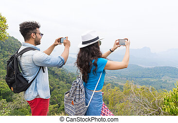 Tourist Couple With Backpack Take Photo Of Landscape From Mountain Top On Cell Smart Phone Back Rear View