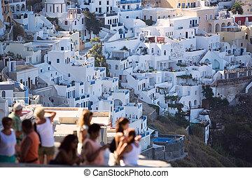 Tourist Destination. Fira main village of greek island Santorini. Tourists blurred unrecognizable.