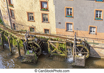 waterfall in the city center of Saarburg, Germany surrounded by houses on a hill
