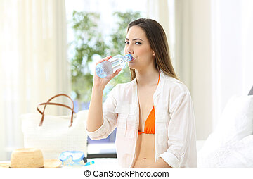 Tourist drinking bottled water in an hotel