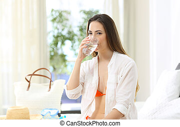 Tourist drinking potable tap water in an hotel room