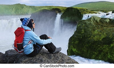 Tourist enjoying the beautiful view of Godafoss waterfall -...