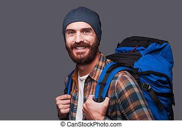 tourist., ficar, barbudo, bonito, mochila, cinzento, contra, jovem, enquanto, carregar, fundo, homem sorridente, feliz