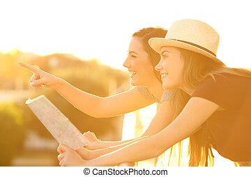 Tourist friends pointing landmarks in hotel balcony
