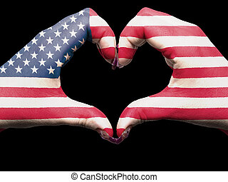 Tourist gesture made by america flag colored hands showing symbol of heart and love