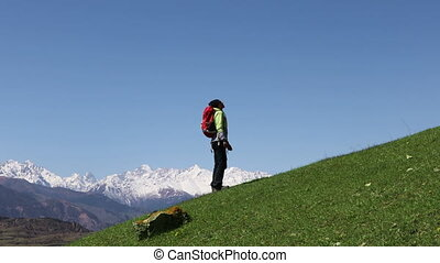 Tourist girl climbs the mountains against the blue sky and...