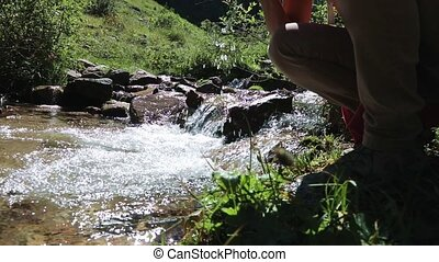 Tourist girl drinking water from a mountain river on a sunny...