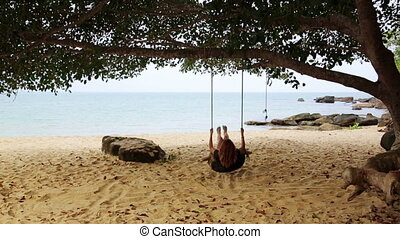 tourist girl enjoying at swing at beach, sihanoukville, cambodia