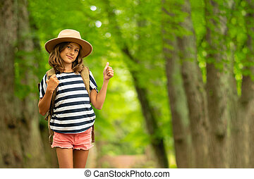 Tourist girl enjoying hiking with backpack in national park. Happy child walking in the forest in summer. Active lifestyle concept