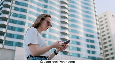 Tourist girl in the summer in Dubai writes a message, looks at a map on the smartphone