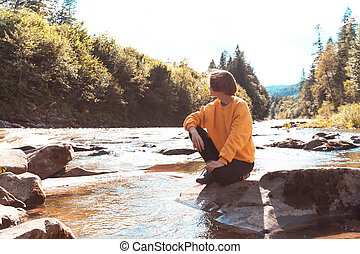 tourist girl sitting on the bank of a mountain river