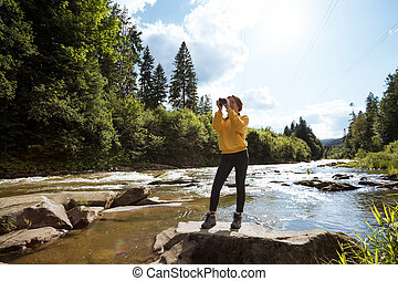 tourist girl standing on the bank of a mountain river