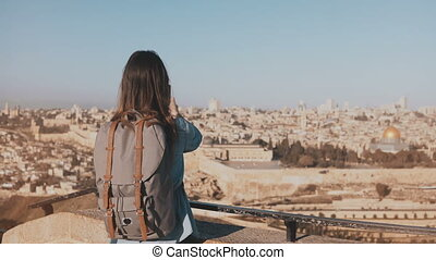 Tourist girl takes photos of old town Jerusalem. Girl with backpack walks to skydeck edge. Capturing moments. Israel 4K.