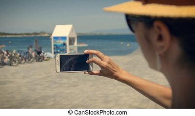 Tourist girl taking a picture in l'Escala port. Costa Brava,...
