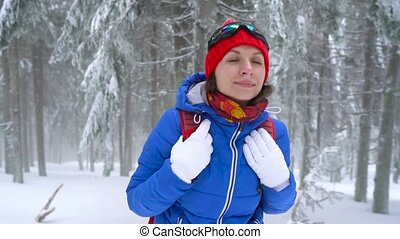 Tourist girl walking on a winter snow-covered coniferous forest in the mountains and reaches out to her companion to help her. Frosty weather