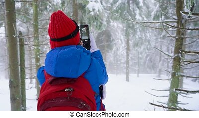 Tourist girl walking on a winter snow-covered coniferous forest in the mountains and takes a photo of nature on a smartphone. Frosty harsh weather