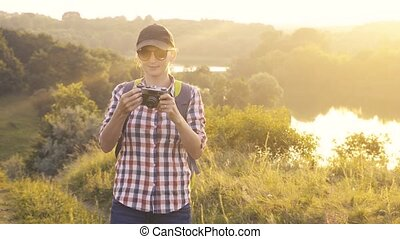 tourist girl with a backpack and a camera walks through a picturesque meadow and photographs the picturesque landscape. Tourism, outdoor activities