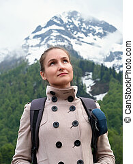 Tourist girl with a backpack on the backdrop of snow-capped mountains