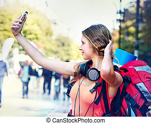 Tourist girl with backpack and headphones taking selfies on smartphone