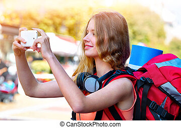 Tourist girl with backpack taking selfies on smartphone