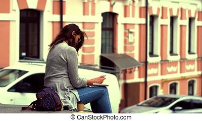 Tourist girl with curly hair taking rest after long walk....