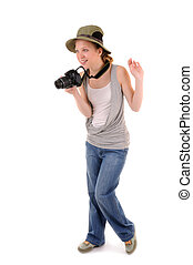 Standing casual smiling girl-tourist with digital photocamera is looking for picture on white background