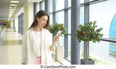 Tourist girl with smartphone in international airport. Airline passenger in an airport lounge waiting for flight aircraft