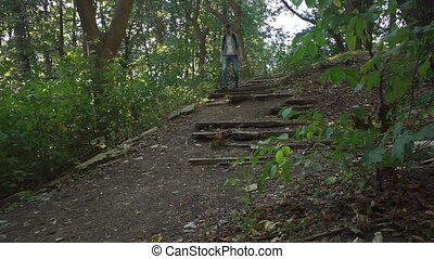 Tourist goes down the old broken stairs in the forest