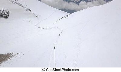 Tourist group climbing a snow mountain peak during winter...