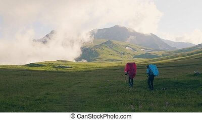 Tourist group walking on green field on mountain landscape background