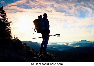 Tourist guide with pole in hand. Hiker with sporty backpack...