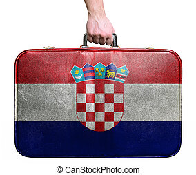 Tourist hand holding vintage leather travel bag with flag of Croatia