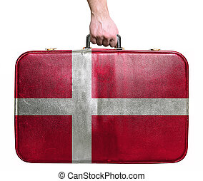 Tourist hand holding vintage leather travel bag with flag of Denmark