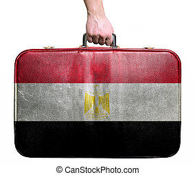 Tourist hand holding vintage leather travel bag with flag of Egypt