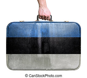 Tourist hand holding vintage leather travel bag with flag of Estonia