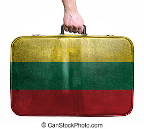 Tourist hand holding vintage leather travel bag with flag of Lithuania