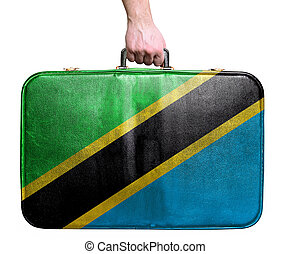 Tourist hand holding vintage leather travel bag with flag of Tanzania