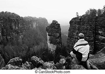 Tourist hiker man on the rock peak in rocky mountains