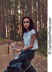 Tourist hipster girl holds a bottle of water, stopped to rest in a beautiful autumn forest.