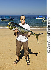 Tourist holding big fish on beach