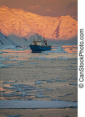 Tourist icebreaker in the light of the Midnight Sun in the Lamaire Channel on the Antarctic Peninsula in Antarctica.