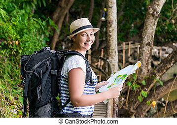 tourist in a hat with a map and a big backpack in the jungle of Asia