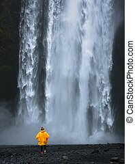 Tourist in a yellow raincoat at the Skogafoss waterfall in Iceland