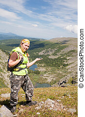 tourist in mountains with a compass in a hand