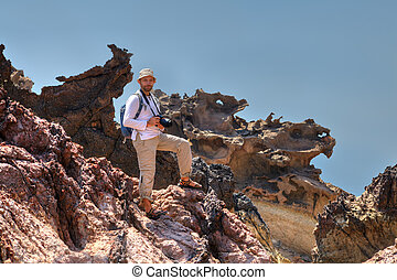 Tourist in panama stands on a rock with the camera.