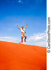Tourist jumping over the sand dunes in Merzouga