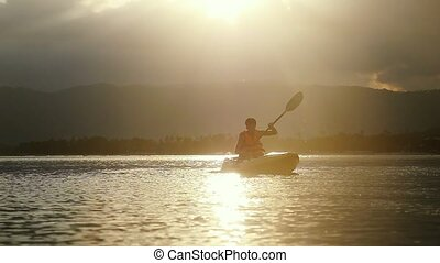 Tourist kayaker paddling at beautiful sunset and water...