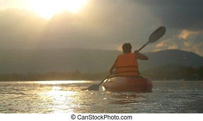 Tourist kayaker paddling at beautiful sunset on tropical...