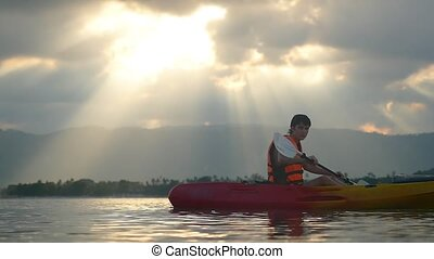 Tourist kayaker paddling at beautiful sunset on tropical...