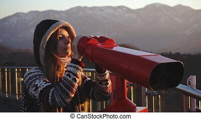 Tourist looking at city through coin-operated binoculars at sunset, medium shot